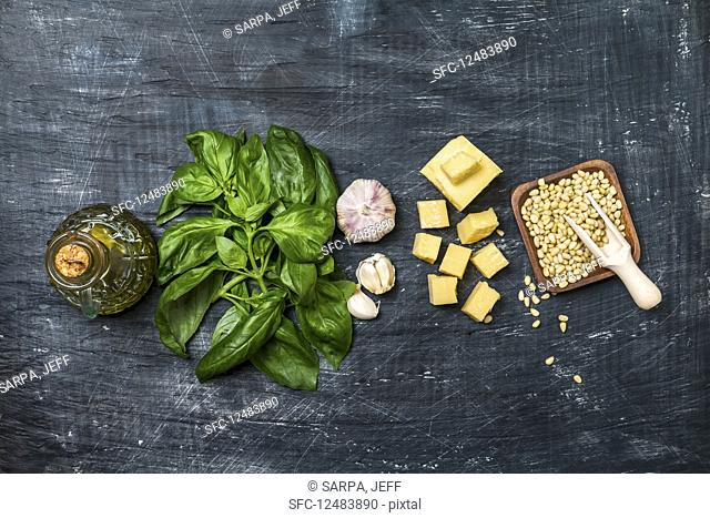 Ingredients for making pesto sauce on a black old background, top view