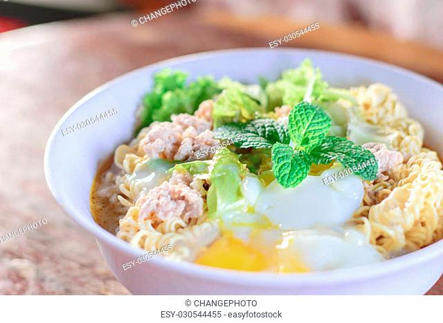 Chinese noodles with minced pork and egg in bowl on wooden table