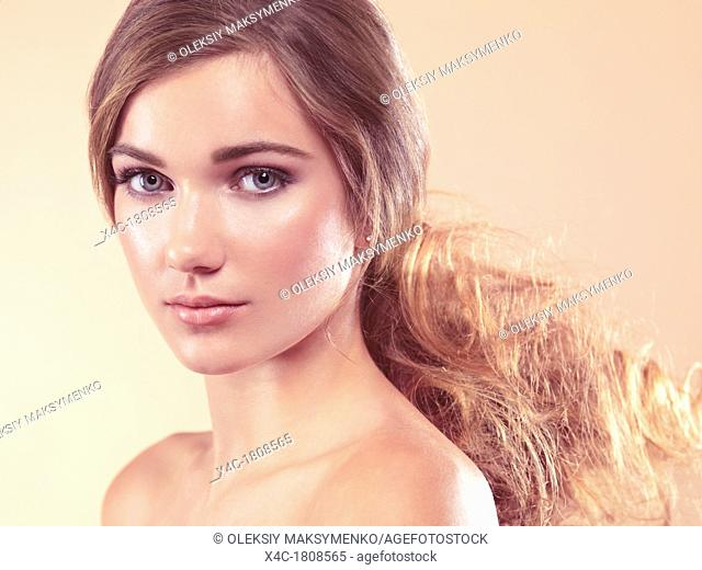 Beauty portrait of a young woman with soft natural look in light beige colors