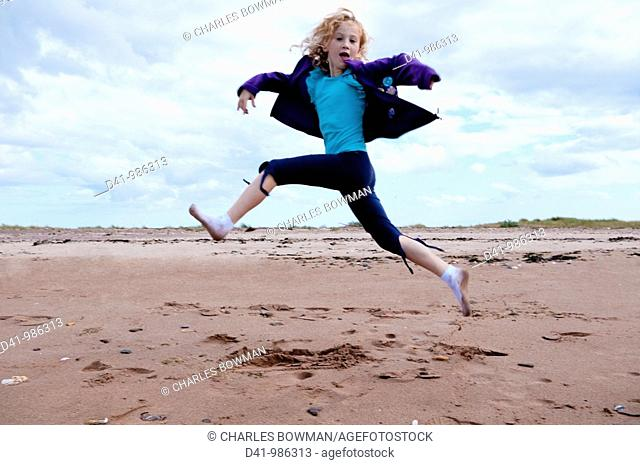 child girl leaping over beach