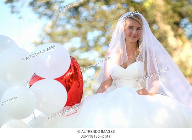 Portrait Of Bride Outdoors With Balloons On Wedding Day