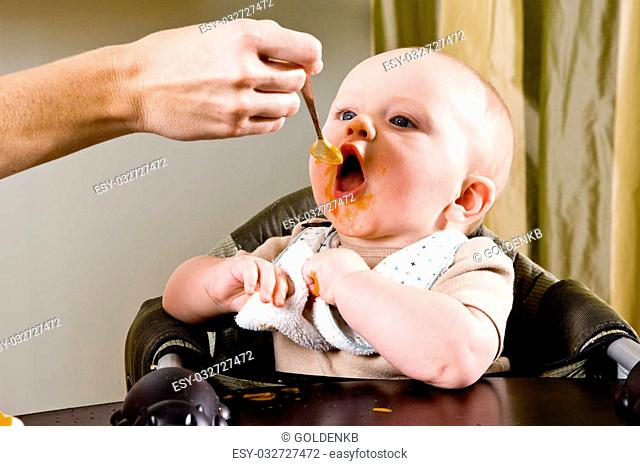 Hungry six month old baby eating solid food from a spoon