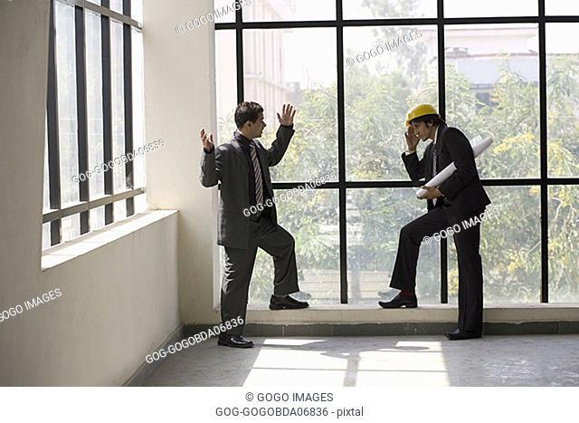 Businessmen talking in an unfinished room