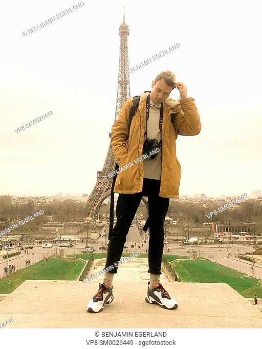 young Millennial tourist with camera standing on platform at Trocadéro next to touristic sight Eiffel Tower, exploring city Paris, France