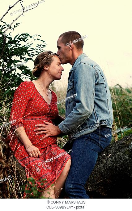 Romantic man kissing pregnant wife's forehead on tree trunk