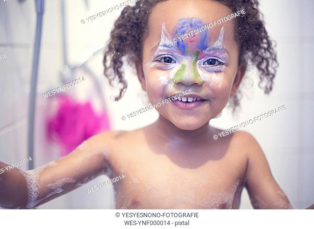 Portrait of smiling little girl with painted face in a bath