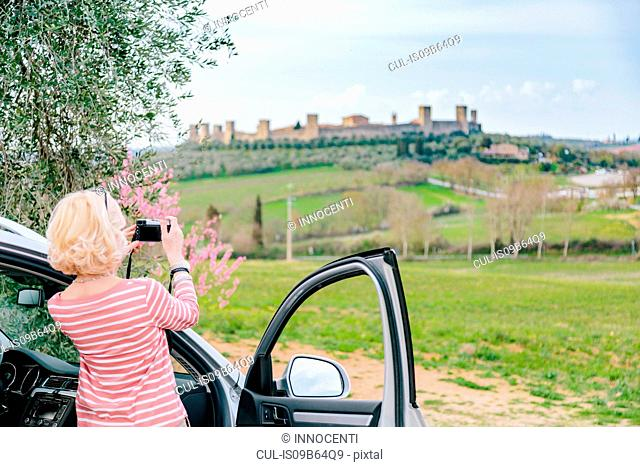 Rear view of female tourist photographing fort in landscape, Siena, Tuscany, Italy