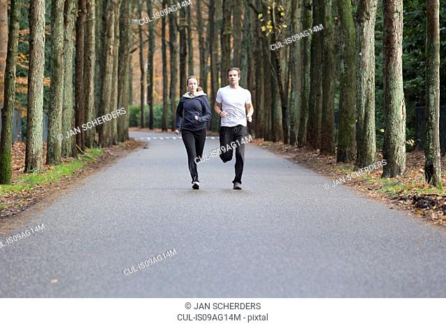 Couple running through forest