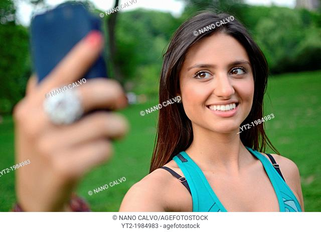 Attractive young mixed race woman taking a self portrait with phone in Central Park, New York City