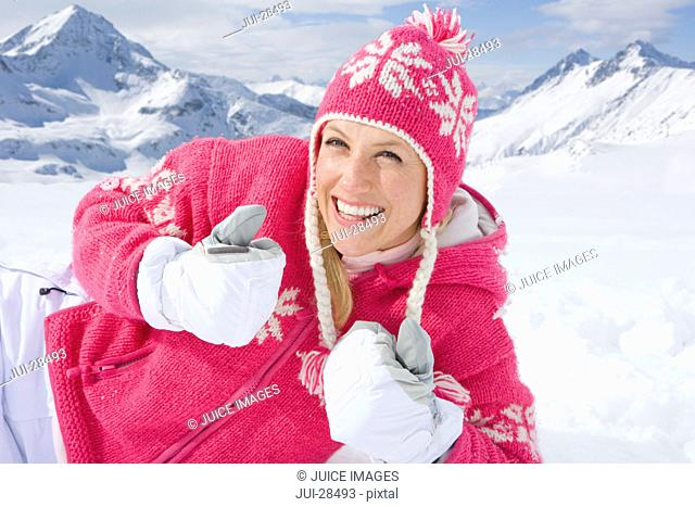 Smiling woman laying in snow in pink sweater and cap giving thumbs up