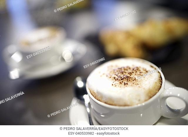 close up of cup of coffee and croissants