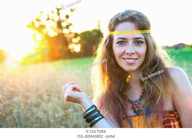 Portrait of mid adult woman wearing hippy clothes, standing in field at sunset, smiling