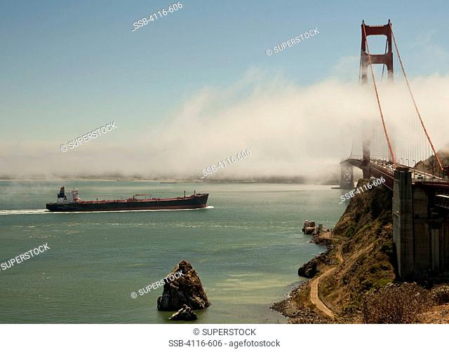 Container ship passing under the Golden Gate Bridge, San Francisco Bay, San Francisco, California, USA