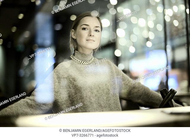 confident woman alone in bar, beautiful bokeh lights, in Munich, Germany