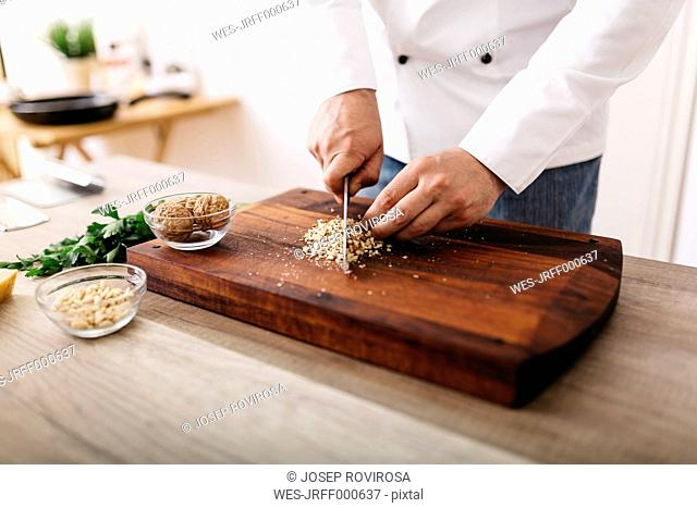 Chef preparing stuffing for ravioli, chopping nuts