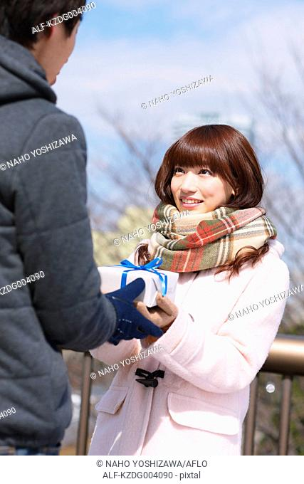 Attractive Japanese woman receiving gift on a Winter day