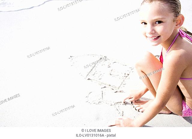 A young girl writing in the sand