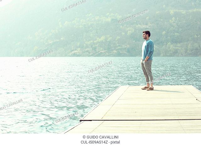 Young man looking out from pier, Lake Mergozzo, Verbania, Piemonte, Italy