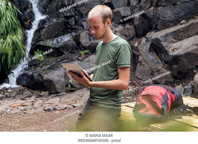 Hiker taking a break at rest area and using tablet, Barranco el Cedro, La Gomera, Canary Islands, Spain