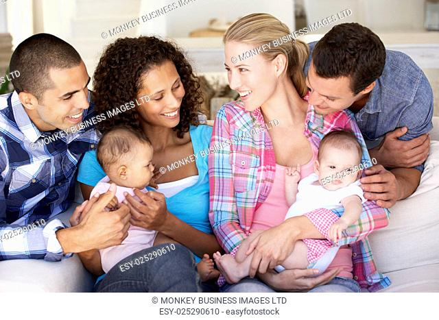 Two Young Family With Babies On Sofa At Home