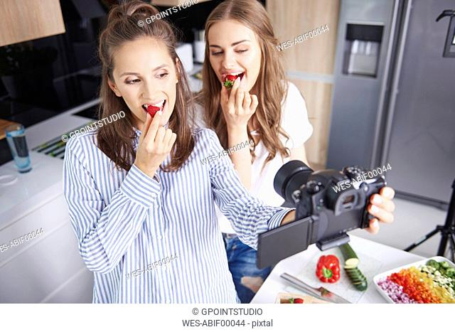 Food bloggers filming theirselves eating strawberries