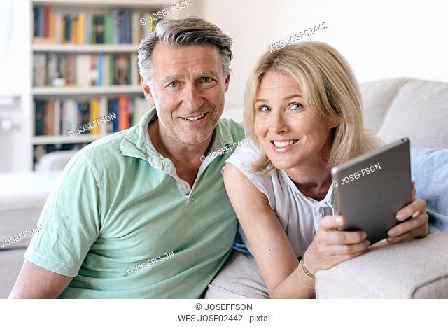 Portrait of smiling mature couple at home with tablet