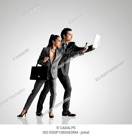 Business couple using cell phone and digital tablet