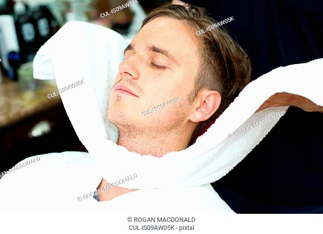 Young man, eye closed having face wrapped in fresh towel