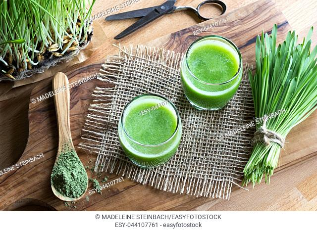 Two glasses of green juice with freshly harvested barley grass in the background