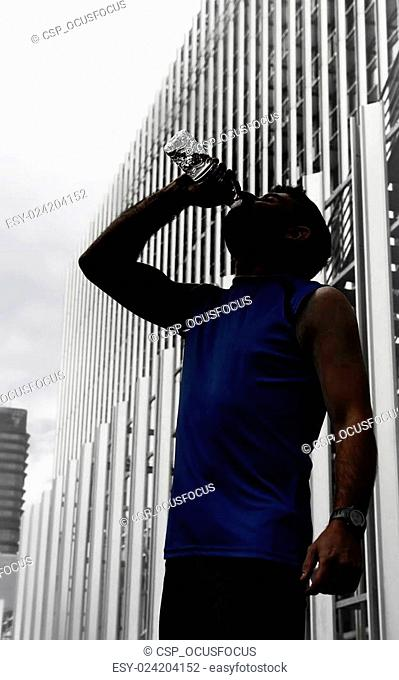 silhouette of young sport man drinking water bottle after running training session in business district