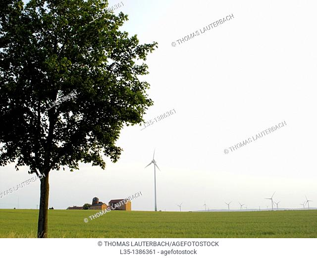 Landscape with an old farmhouse and modern wind generators, Lower Saxony, Germany