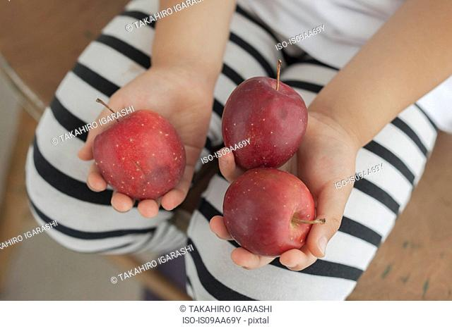 Girl holding three red apples, high angle