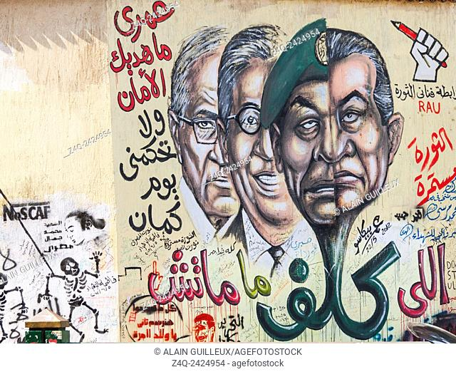 Egypt, Cairo, graffiti of the Egyptian revolution on Mohamed Mahmoud Street. The 2 half faces state that the previous ruler and the current one are so close...