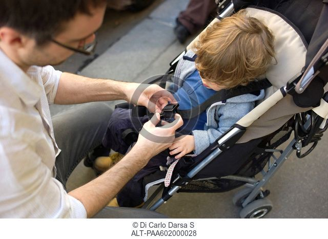 Father strapping toddler boy into stroller