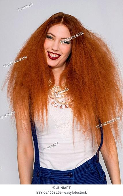 Female model with red lipstick playing with frizzy hair on white background