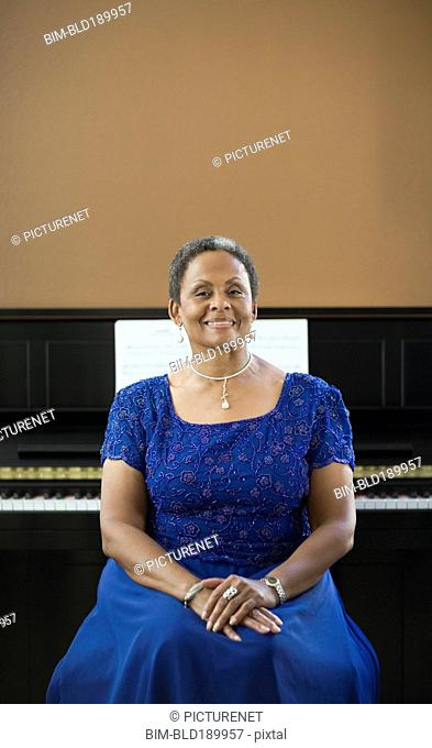 African woman in evening gown sitting in front of piano