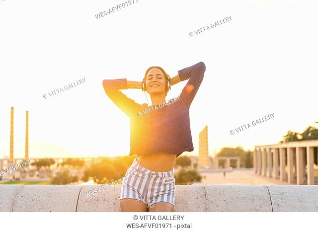 Spain, Barcelona, Montjuic, happy young woman listening to music with headphones at sunset