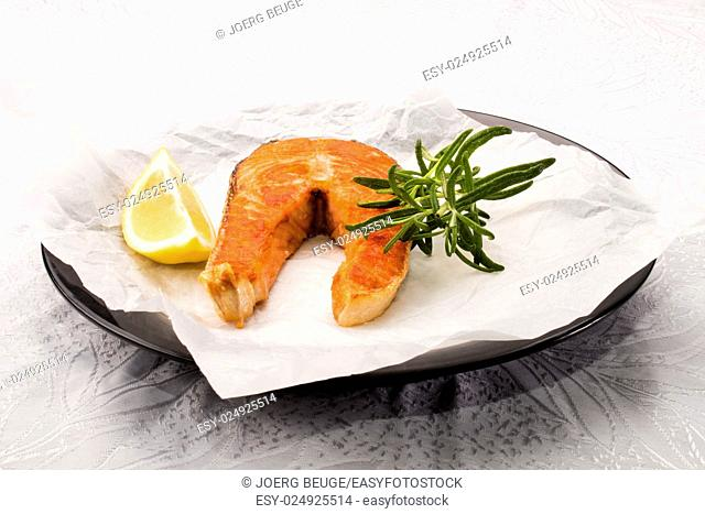 fried scottish salmon steak with rosemary and white kitchen paper on a plate