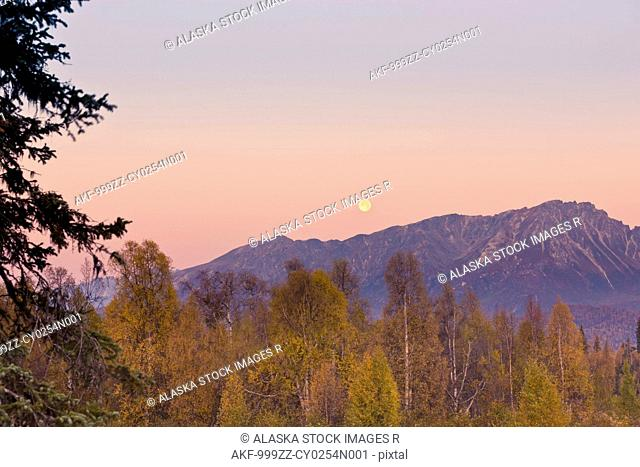 The full moon sets over the foothills of the Alaska Range as seen from the Veterans Memorial in Denali State Park, Southcentral Alaska, Autumn