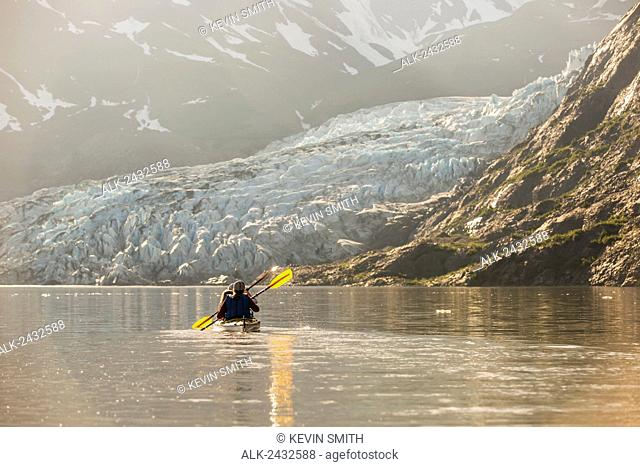 Sea kayakers paddling in evening light at Shoup Bay State Marine Park, Prince William Sound, Valdez, Southcentral Alaska