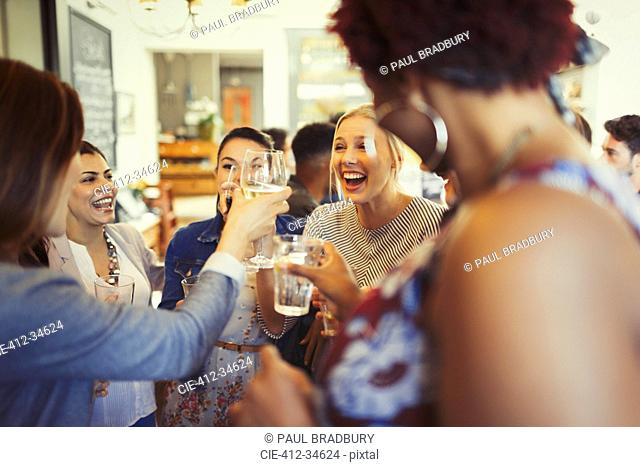 Enthusiastic women friends toasting wine glasses at bar