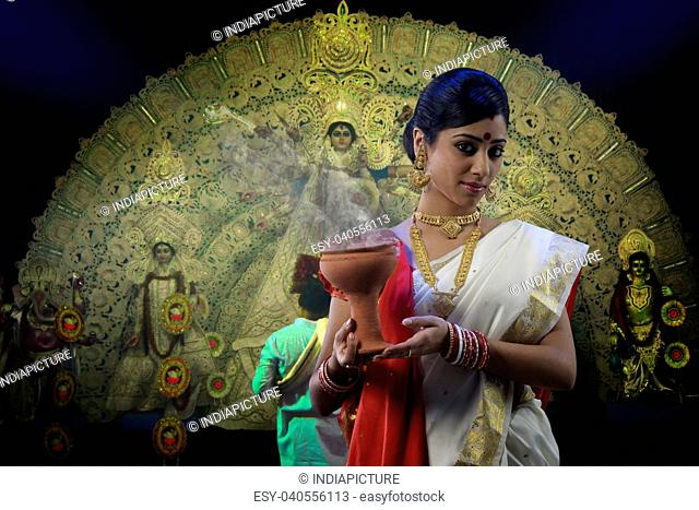 Bengali woman holding a dhunuchi