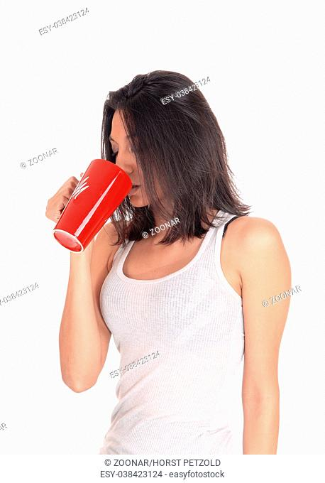 Hispanic woman drinking from a red mug