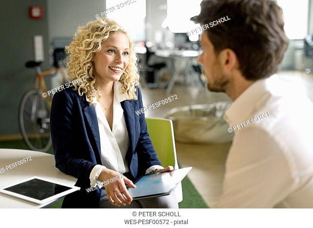 Businessman and woman discussing project in office, using digital tablet