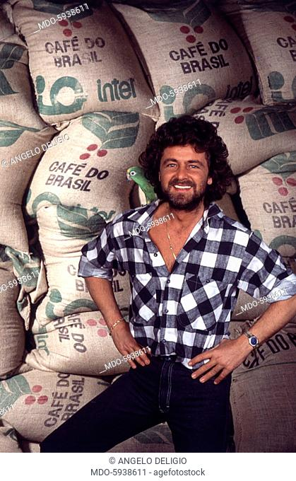 The comedian Beppe Grillo smiling in front of some coffee bags in the Tv show Te lo do io il Brasile. 1984