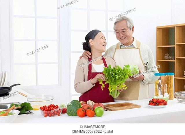 Senior couple holding vegetables in the kitchen and smiling happily
