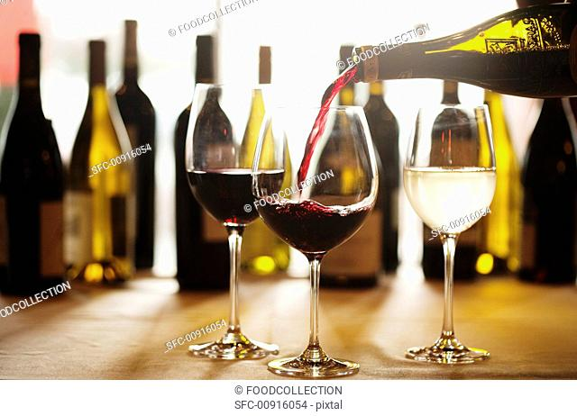 Red Wine Pouring into a Glass from Bottle, Glasses and Bottles of Wine