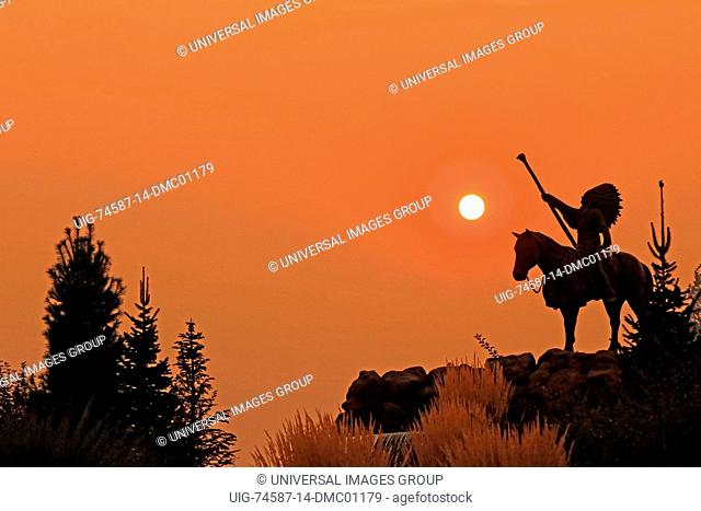 Statue of Native American warrior on horse at sunset