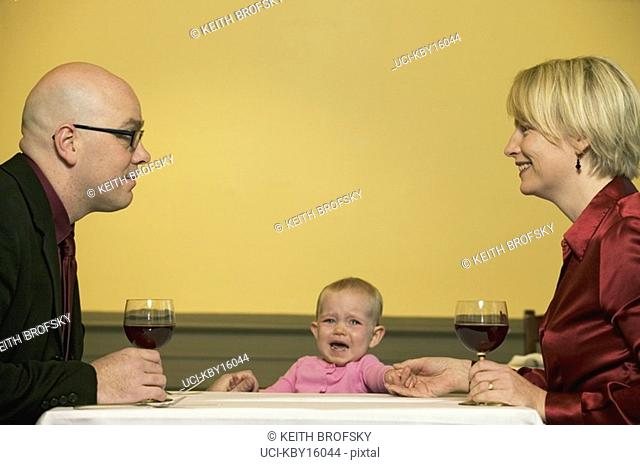 Couple enjoying romantic dinner despite crying baby