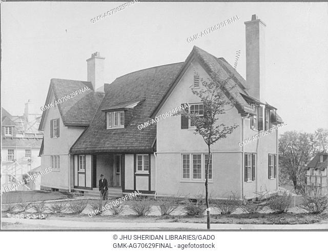 Angled frontal view of home next to quiet street lined with small bushes and young trees, surrounded by other homes, appears to be two stories tall with two...